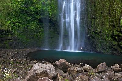 Woman sitting under Hi'ilawe Waterfall, Hawaii
